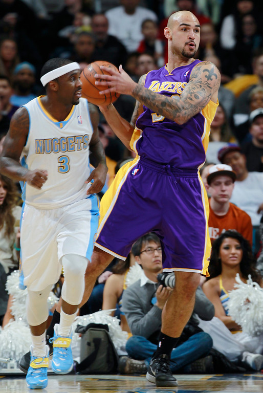 . Los Angeles Lakers center Robert Sacre, back, pulls in loose ball in front of Denver Nuggets guard Ty Lawson in the first quarter of an NBA basketball game in Denver on Friday, March 7, 2014. (AP Photo/David Zalubowski)