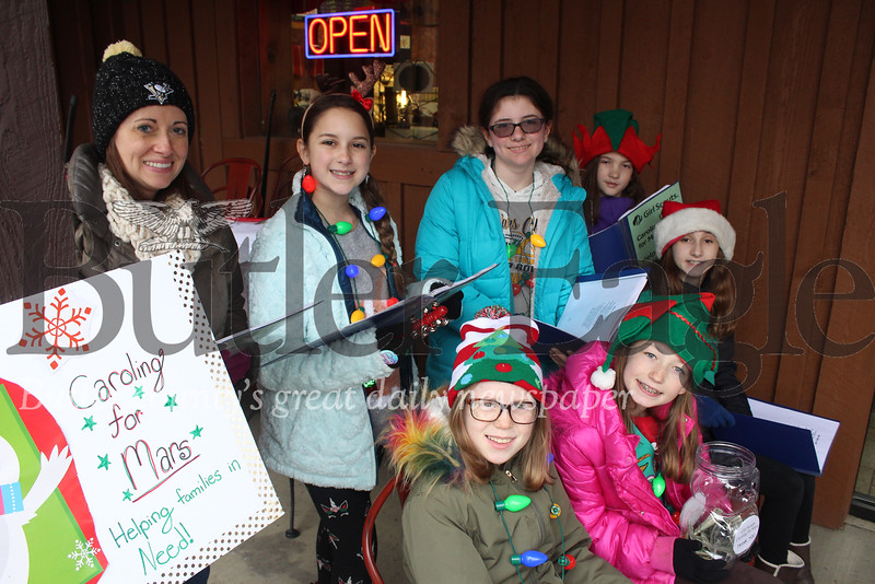 Mars Girl Scout Troop 28842 sang Christmas Carols collecting money for the less fortunate Saturday morning outside a local business. (Dave's Meats along Route 8)  From left, Troop Leader Melissa Steiner, Anya Peck, 11, Makenna Steiner, 11, Rachel Snyder, 10; Sitting (L-R): Lauren Chadwick,10, Grace Wilson, 10, and Madeline James, 11. Harold Aughton/Special to the Eagle