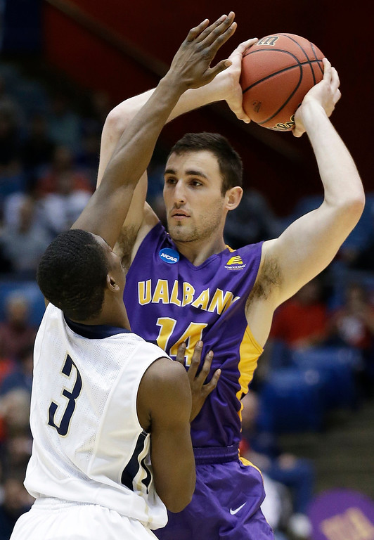 . Albany forward Sam Rowley (14) is pressured by Mount St. Mary\'s guard Sam Prescott (3) in the first half of a first-round game of the NCAA college basketball tournament, Tuesday, March 18, 2014, in Dayton, Ohio. (AP Photo/Al Behrman)