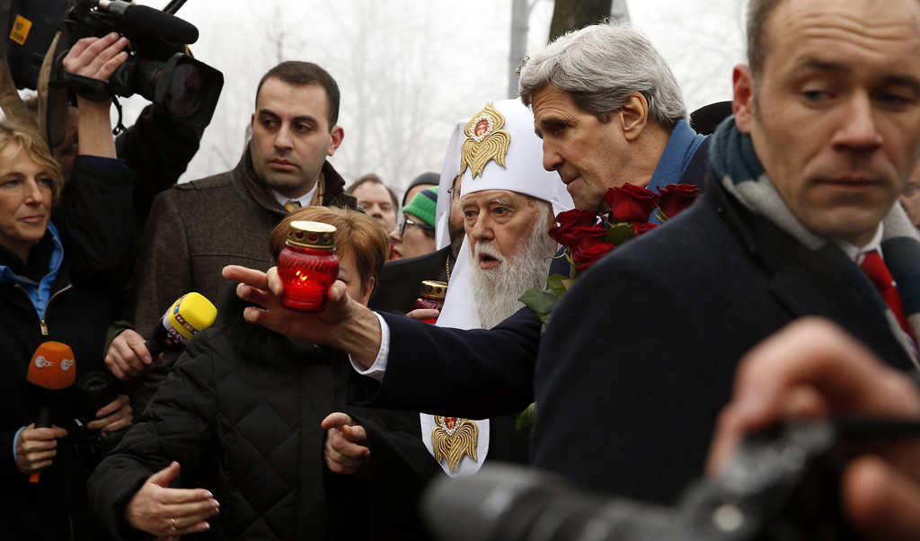 . US Secretary of State John Kerry speaks with Ukraine\'s Patriarch Filaret before placing a candle at the Shrine of the Fallen in Kiev on March 4, 2014. AFP PHOTO / POOL - Kevin LAMARQUE/AFP/Getty Images