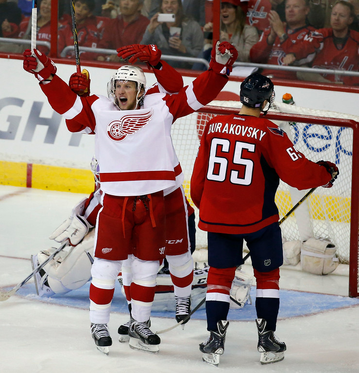 . Detroit Red Wings left wing Justin Abdelkader, left, celebrates his goal as Washington Capitals left wing Andre Burakovsky (65), from Austria, stands nearby, in the third period of an NHL hockey game, Wednesday, Oct. 29, 2014, in Washington. Abdelkader had two goals in the third period. The Red Wings won 4-2. (AP Photo/Alex Brandon)