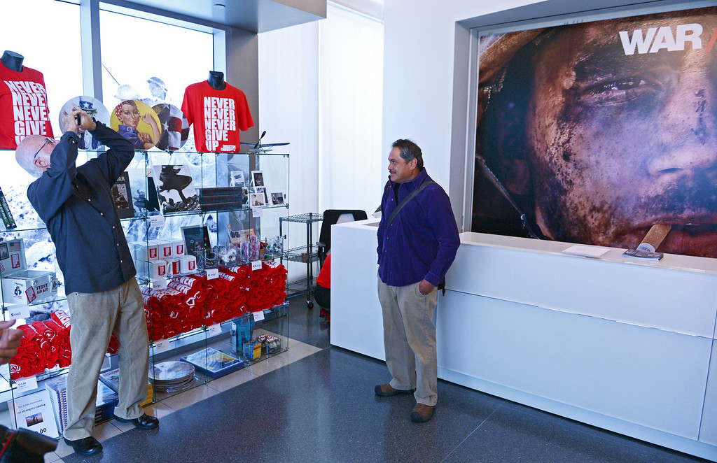 . Photographer David Hume Kennerly makes a phone snapshot of photographer Luis Sinco with his photograph at the exhibit: WAR/Photography - Images of Armed Conflict and its Aftermath. Photography exhibit at the Annenberg Space for Photography. Photo by Brad Graverson 3-20-13