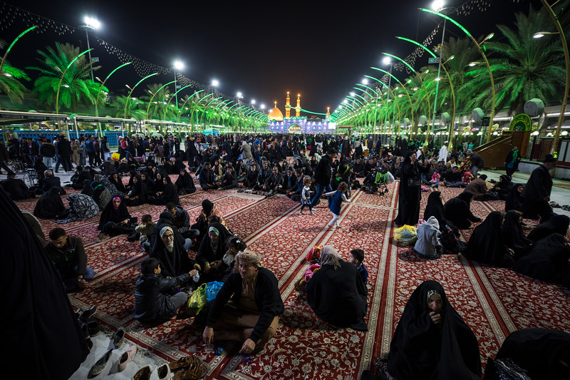 Families enjoying the cool evening temperature with the Shrine of Imam Husayn ibn Ali in the distance.