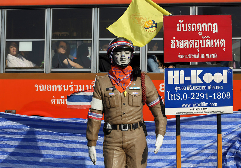 . City bus passengers look at a life-size figure of a traffic policeman erected at victory monument intersection, a site Thai anti-government protesters stage a rally at, Tuesday, Jan. 21, 2014 in Bangkok, Thailand. Twin explosions shook an anti-government demonstration site in Thailand\'s capital, wounding dozens of people in the latest violence to hit Bangkok as the nation\'s increasingly bloody political crisis drags on. (AP Photo/Apichart Weerawong)