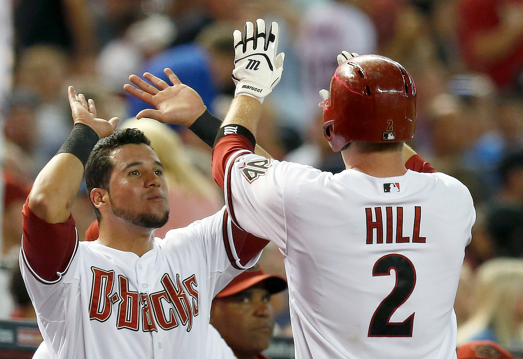 . Arizona Diamondbacks\' Aaron Hill (2) gets high-fives from teammate David Peralta after Hill hit a home run against the Detroit Tigers during the first inning of a baseball game on Tuesday, July 22, 2014, in Phoenix. (AP Photo)
