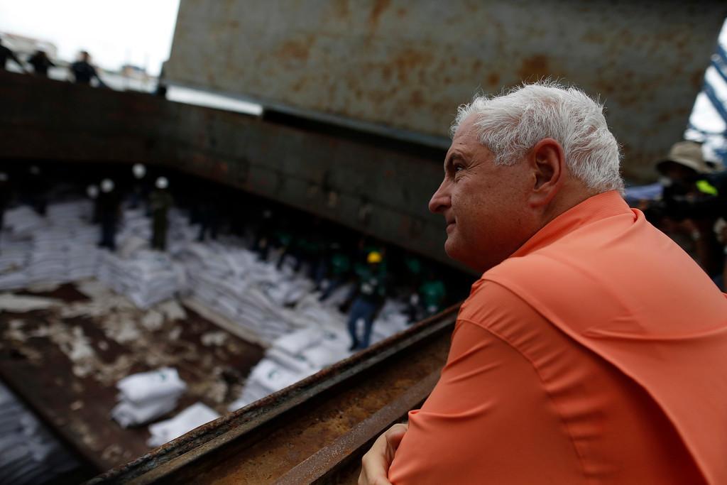 ". Panama\'s President Ricardo Martinelli look at bags labeled \""Cuban Raw Sugar\"" inside a North Korean flagged ship \""Chong Chon Gang\"" docked at the Manzanillo Container Terminal in Colon City July 16, 2013. REUTERS/Carlos Jasso"