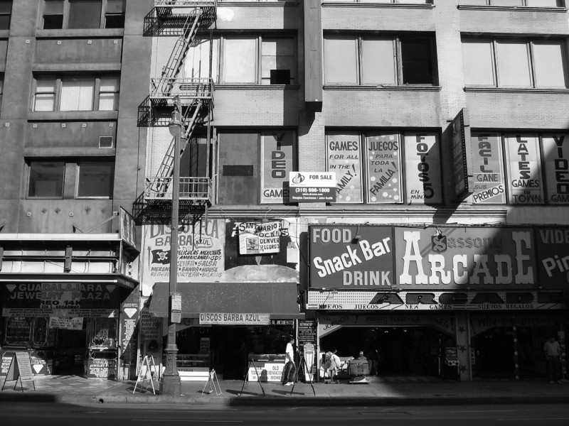 Downtown Los Angeles, Broadway. A slum  Broadway - Downtown Los Angeles, California.  Made with my point and shoot Canon PowerShot SD500 at it's widest.  Notice the slight bend in the horizontal lines caused by the small lens in this excellent camera.   This area was the epicenter of L.A. culture during the 20's.  LA was a city that rivaled all others during that time.   Today it's a slum thanks to Californian politicians who favor