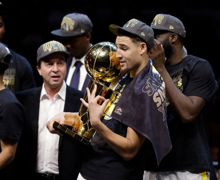 . Golden State Warriors\' Klay Thompson gestures while holding the trophy after the Warriors defeated the Cleveland Cavaliers 108-85 in Game 4 of basketball\'s NBA Finals to win the NBA championship, Friday, June 8, 2018, in Cleveland. (AP Photo/Tony Dejak)