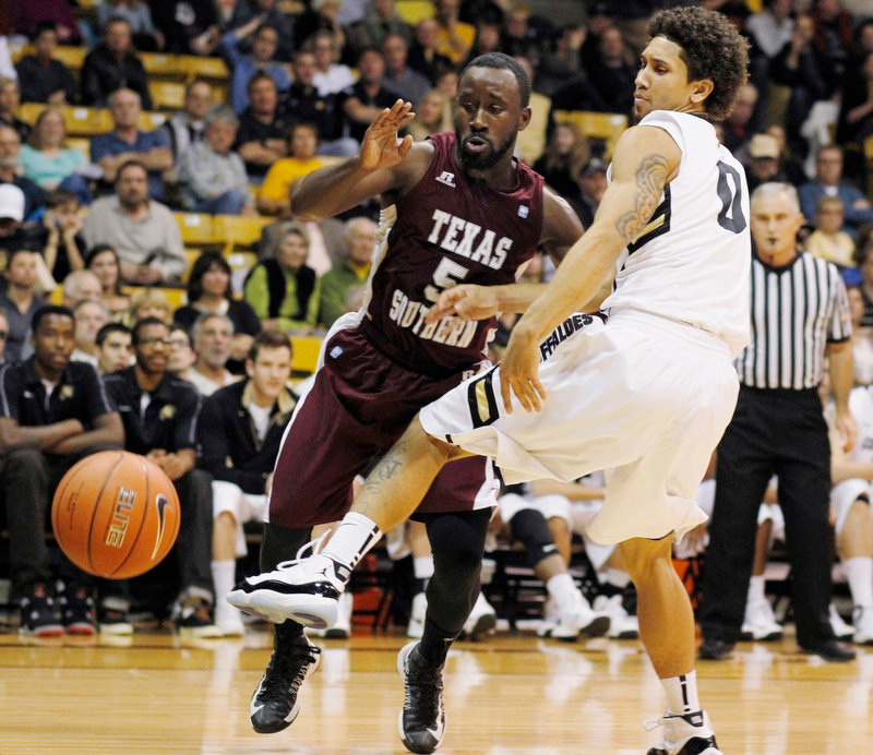 . Texas Southern guard Omar Strong, left, has the ball swatted out of his hands by Colorado guard Askia Booker in the first half of an NCAA college basketball game in Boulder, Colo., on Tuesday, Nov. 27, 2012. (AP Photo/David Zalubowski)