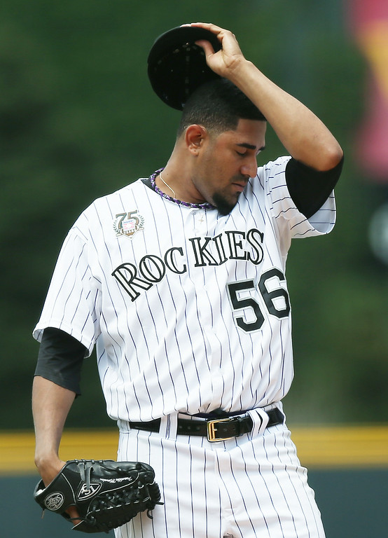 . Struggling with the heat and humidity, Colorado Rockies starting pitcher Franklin Morales wipes his brow while facing the Pittsburgh Pirates in the first inning of a baseball game in Denver on Sunday, July 27, 2014. (AP Photo/David Zalubowski)