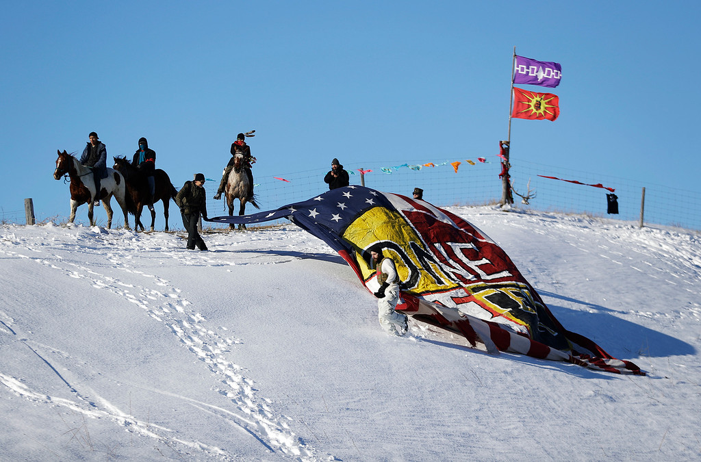 """. Veterans unveil a banner that reads \""""One Water\"""" on a hillside across from the Oceti Sakowin camp where people have gathered to protest the Dakota Access oil pipeline in Cannon Ball, N.D., Sunday, Dec. 4, 2016. Tribal elders have asked the military veterans joining the large Dakota Access pipeline protest encampment not to have confrontations with law enforcement officials, an organizer with Veterans Stand for Standing Rock said Sunday, adding the group is there to help out those who\'ve dug in against the four-state, $3.8 billion project. (AP Photo/David Goldman)"""