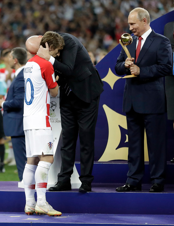 . FIFA President Gianni Infantino embraces Croatia\'s Luka Modric as Russian President Vladimir Putin holds the player of the tournament award before presenting it to him after the final match between France and Croatia at the 2018 soccer World Cup in the Luzhniki Stadium in Moscow, Russia, Sunday, July 15, 2018. France won the final 4-2. (AP Photo/Matthias Schrader)