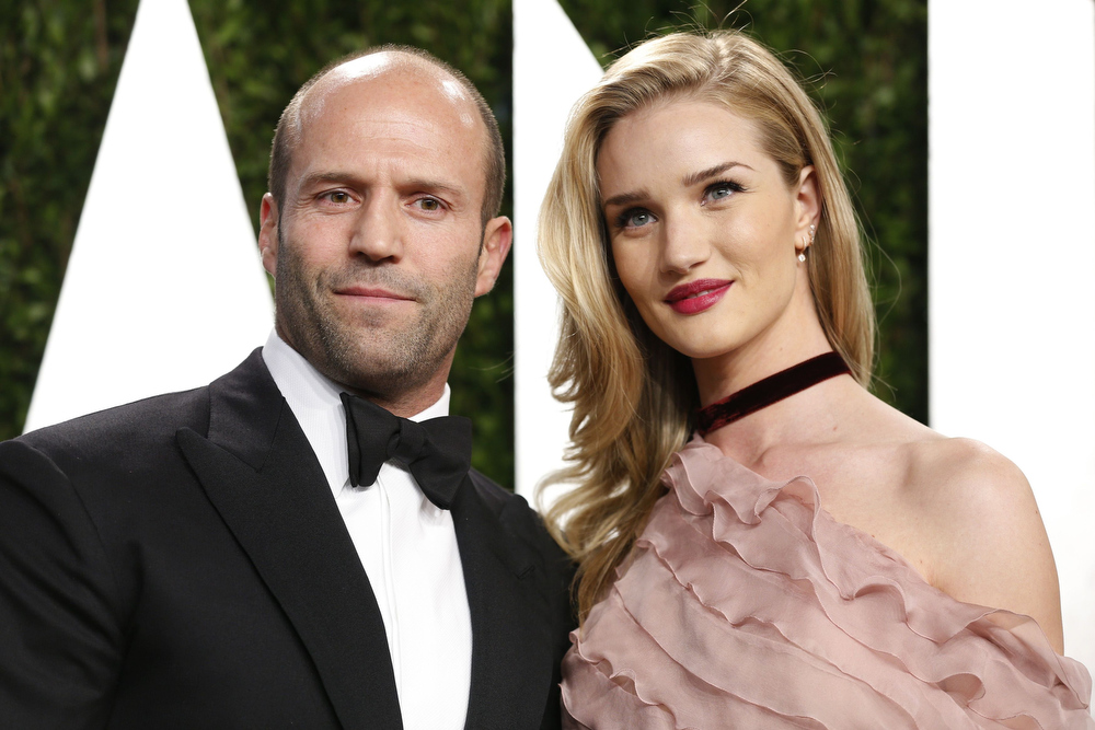 Description of . Jason Statham (L) with girlfriend Rosie Huntington-Whiteley attend the 2013 Vanity Fair Oscars Party in West Hollywood, California February 24, 2013.  REUTERS/Danny Moloshok