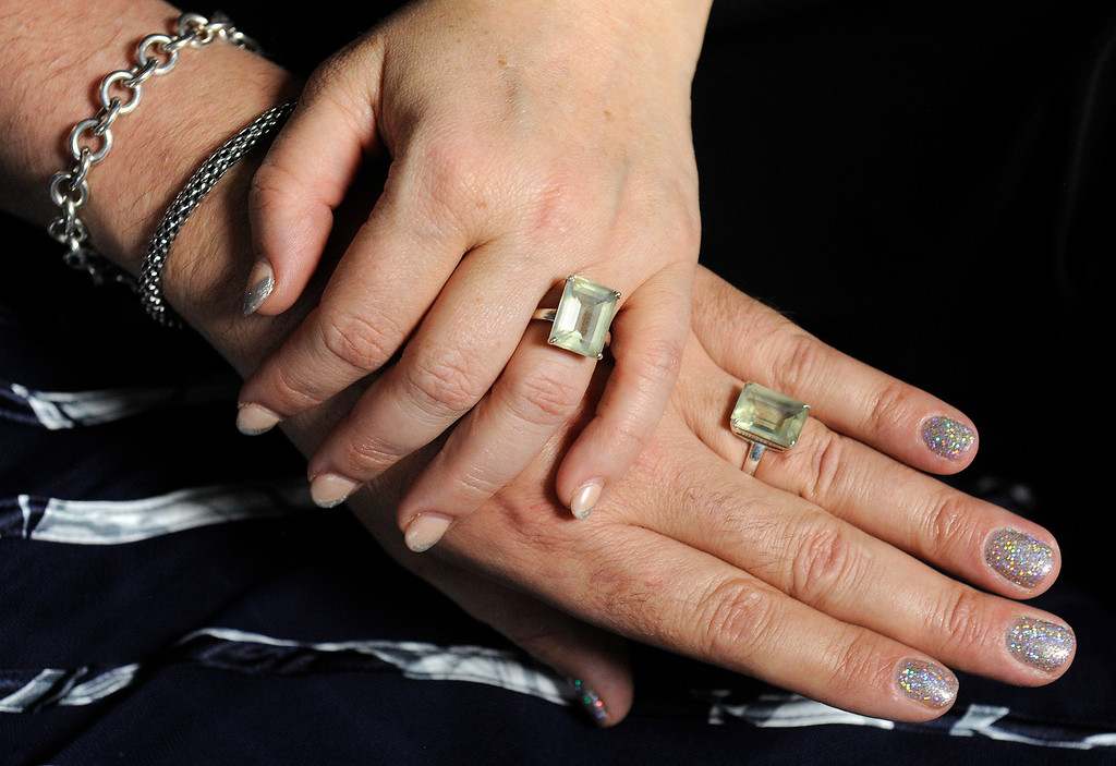 . The hands of  Koko, lower right,  and Sara Brentano on Monday, June 17, 2013 at Koko\'s Denver photo studio. Koko wears more jewelry in this photo with their wedding rings. (Photo By Cyrus McCrimmon/The Denver Post)