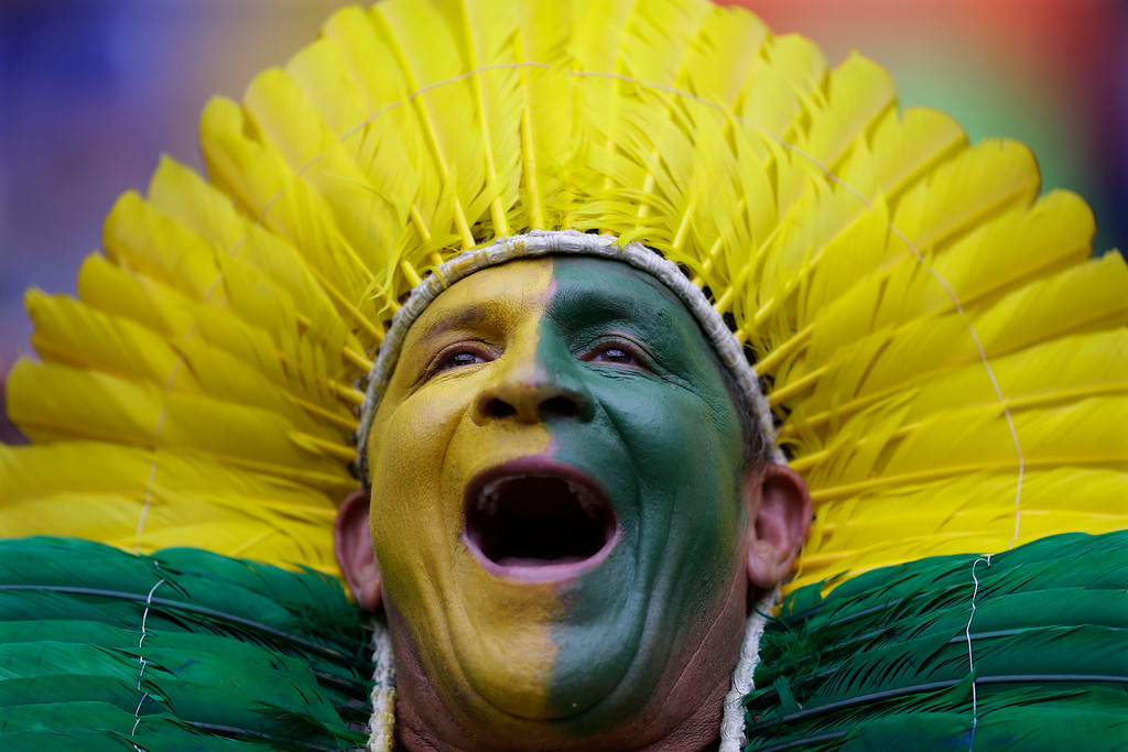 . A Brazil supporter cheers for the national team before the group A World Cup soccer match between Cameroon and Brazil at the Estadio Nacional in Brasilia, Brazil, Monday, June 23, 2014. (AP Photo/Natacha Pisarenko)