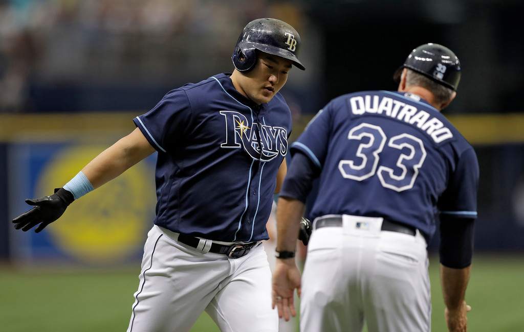 . Tampa Bay Rays\' Ji-Man Choi, of South Korea, left, celebrates with third base coach Matt Quatraro after Choi hit a two-run home run off Cleveland Indians pitcher Carlos Carrasco during the first inning of a baseball game Wednesday, Sept. 12, 2018, in St. Petersburg, Fla. (AP Photo/Chris O\'Meara)