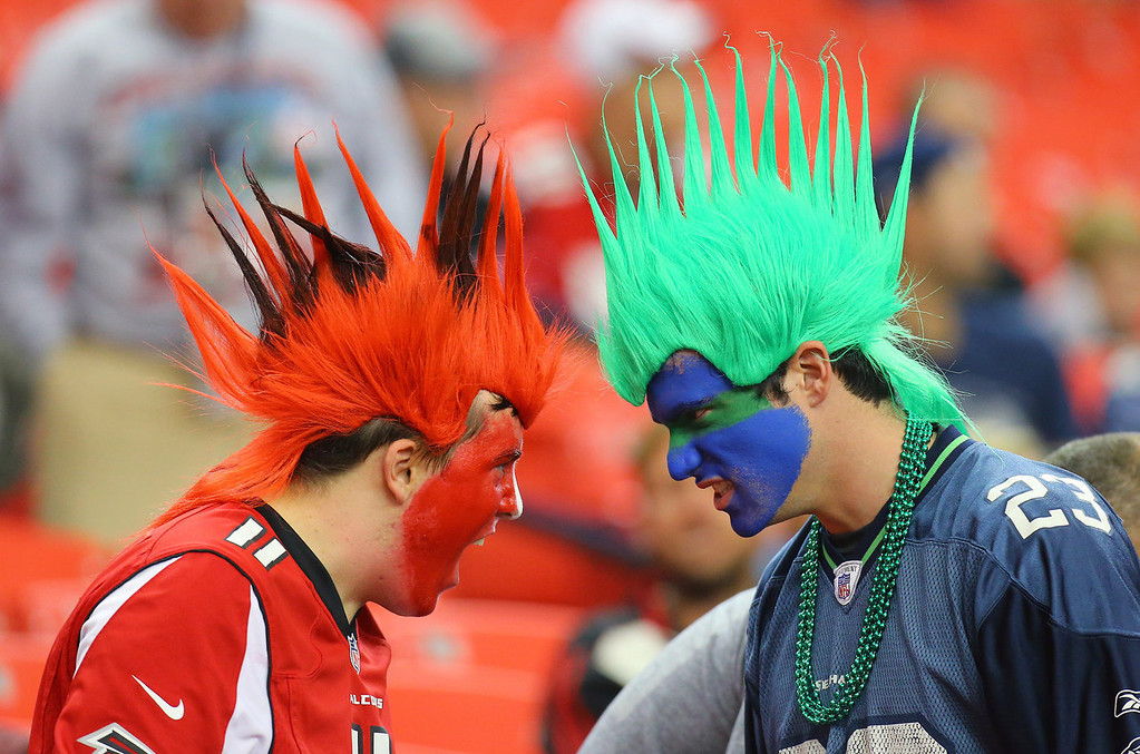 . An Atlanta Falcons fan and a Seattle Seahawks fan face-off during the second half of a NFL football game on Sunday, Nov. 10, 2013, in Atlanta. (AP Photo/Atlanta Journal-Constitution, Curtis Compton)