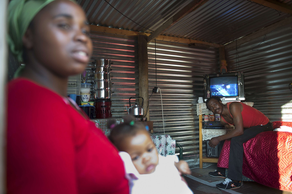 . A miner and his family are seen in their shack on July 9, 2013 in the Nkaneng shantytown next to the platinum mine, run by British company Lonmin, in Marikana. On August 16, 2012, police at the Marikana mine open fire on striking workers, killing 34 and injuring 78, during a strike was for better wages and living conditions. Miners still live in dire conditions despite a small wage increase.  ODD ANDERSEN/AFP/Getty Images