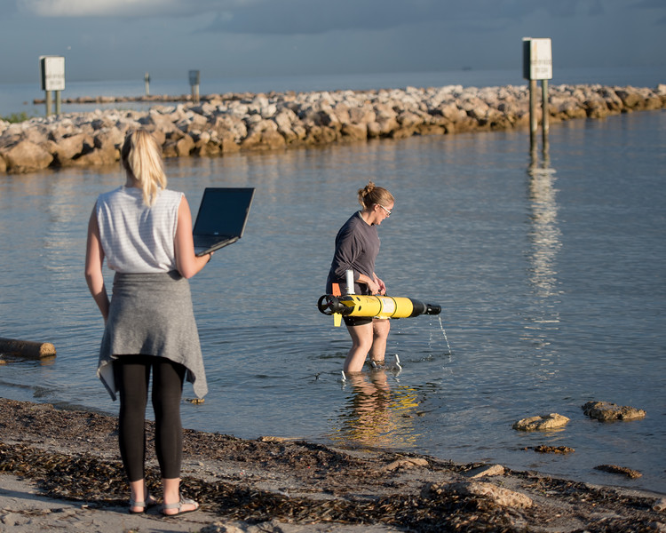 Jessica Tolan (left) and Emily Cira - research technicians under Dr. Wetz life sciences program. Release the ECO Mapper an autonomous underwater vehicle (AUV) used to collect data to survey bodies of water.