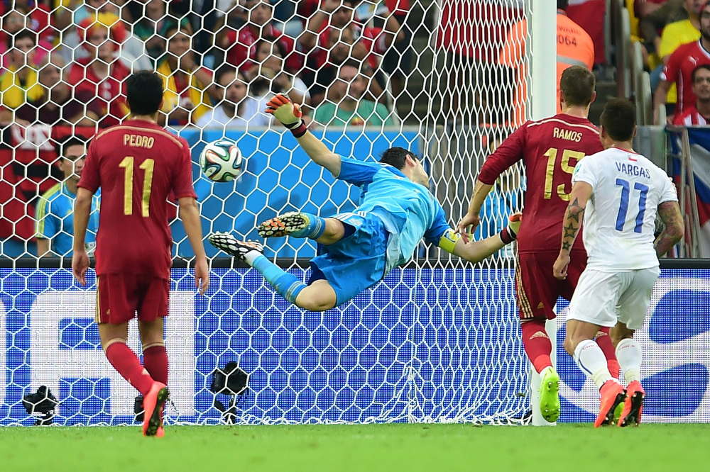 . Spain\'s goalkeeper and captain Iker Casillas (C) fails to save a goal during a Group B football match between Spain and Chile in the Maracana Stadium in Rio de Janeiro during the 2014 FIFA World Cup on June 18, 2014.  (MARTIN BERNETTI/AFP/Getty Images)