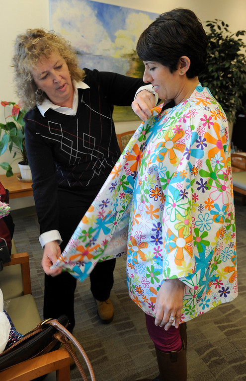 . (l-r) Brenda Jones helps to put a Hug Wrap on patient Liz Barnett. Jones created her own open-in-the-front wrap when she was undergoing treatment for breast cancer, crafting an option to the hospital gown, utilizing soft and colorful flannel fabrics. Fellow patients loved them and her nonprofit Hug Wraps was born. Jones visited Providence Saint Joseph Medical Center�s Roy and Patricia Disney Family Cancer Center and gave patients free wraps. Burbank, CA 2/22/2013(John McCoy/Staff Photographer)