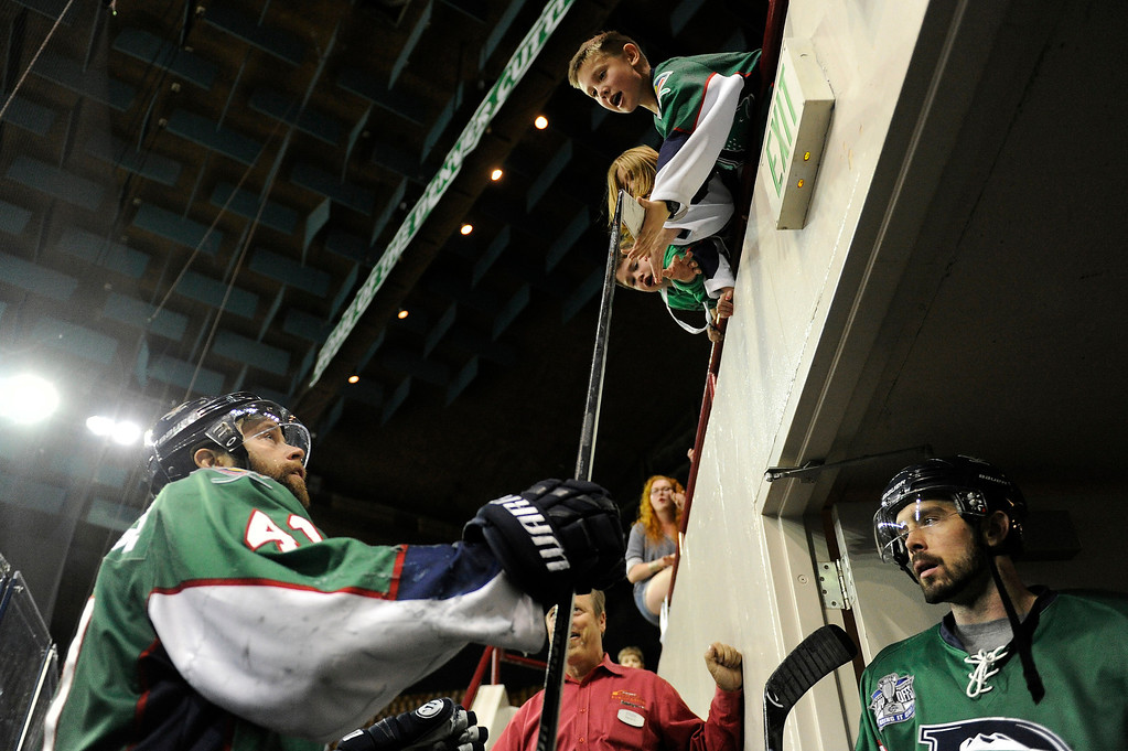 . DENVER, CO - MAY 2: Garett Bembridge (41) of the Denver Cutthroats gives a fan a stick high five to a fan as the Cutthroats leave the ice after defeating the Allen Americans 5-4 in game 1 of the Ray Miron Presidents Cup Finals at the Denver Coliseum in Denver, Colorado on May 2, 2014. (Photo by Seth McConnell/The Denver Post)