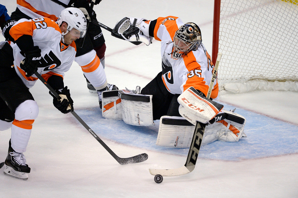 . Philadelphia Flyers goalie Steve Mason (35) pokes at the puck as Philadelphia Flyers defenseman Mark Streit (32) comes in to push it out during the second period against the Colorado Avalanche January 2, 2014 at Pepsi Center. (Photo by John Leyba/The Denver Post)