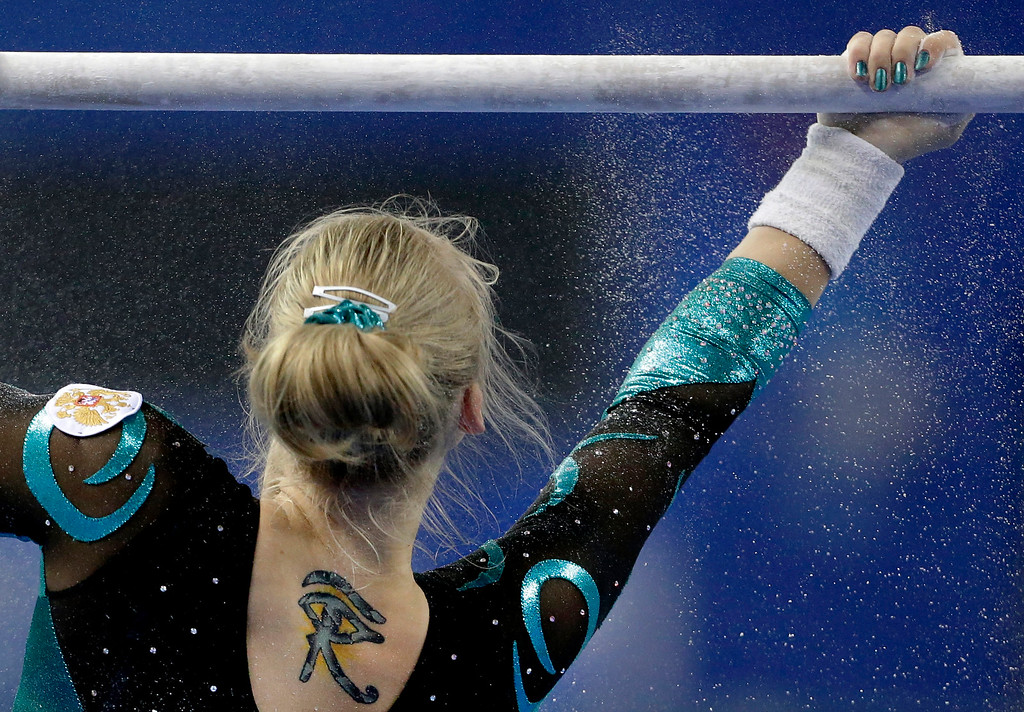 . Russia\'s Tatiana Nabieva puts powder on the uneven bars before competing in the women\'s qualifying round of the Artistic Gymnastics World Championships at the Guangxi Gymnasium in Nanning, capital of southwest China\'s Guangxi Zhuang Autonomous Region Sunday, Oct. 5, 2014. (AP Photo/Andy Wong)
