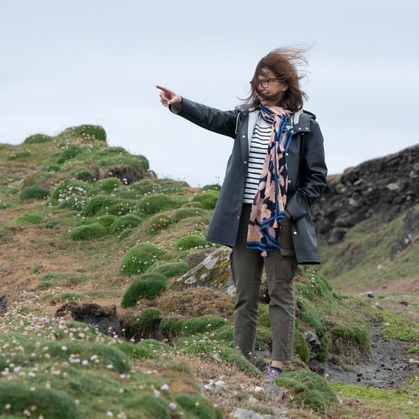 Woman standing on coast pointing her finger, Achill Island, County Mayo, Ireland