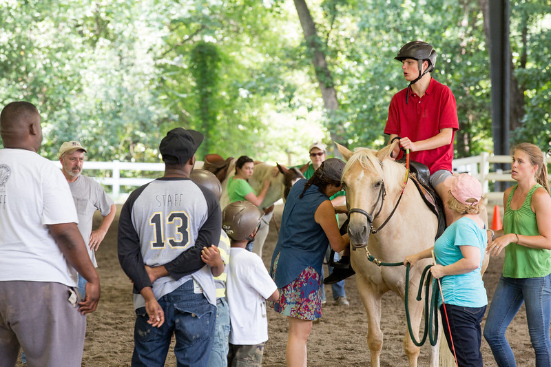 With help from the group, Michael Sullivan learns a little about horseback riding at Chastain Horse Park.  The center provides therapeutic programs for special needs campers and for those in need of physical and occupational therapies.  The program is comprised of professional therapist, equestrians and volunteers.    (Jenni Girtman / Atlanta Event Photography)