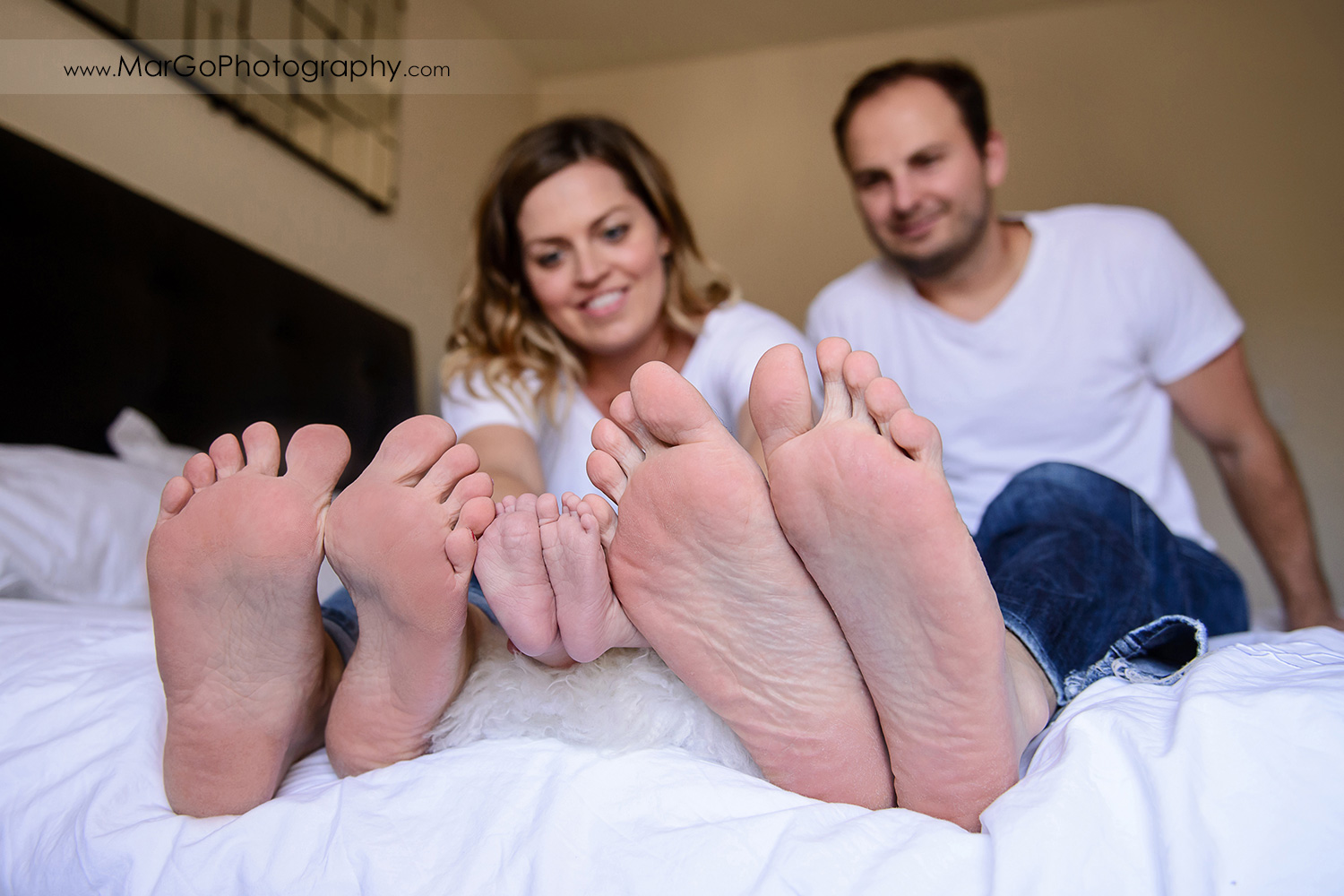 feet shot of family of three in white T-shirts and jeans during newborn session