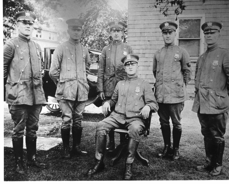 1917 Police force. Chief Charles Hopkins in the chair. This could be in front of the chief's residence on West Chestnut St.