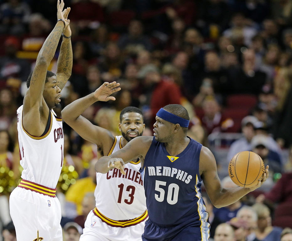 . Memphis Grizzlies\' Zach Randolph (50) looks to pass around Cleveland Cavaliers\' DeAndre Liggins (14) and Tristan Thompson (13) in the first half of an NBA basketball game Tuesday, Dec. 13, 2016, in Cleveland. (AP Photo/Tony Dejak)