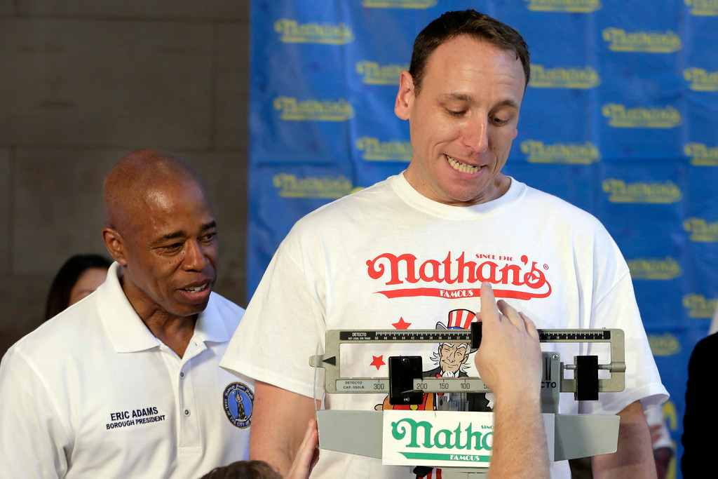 . Current men\'s champion Joey Chestnut, right, of San Jose, Calif., watches the scale during his weigh-in for the 2017 Nathan\'s Hot Dog Eating Contest, in Brooklyn Borough Hall, in New York, Monday, July 3, 2017. Looking on with him is Brooklyn Borough President Eric Adams. Chestnut weighed-in at 221.5 pounds. (AP Photo/Richard Drew)