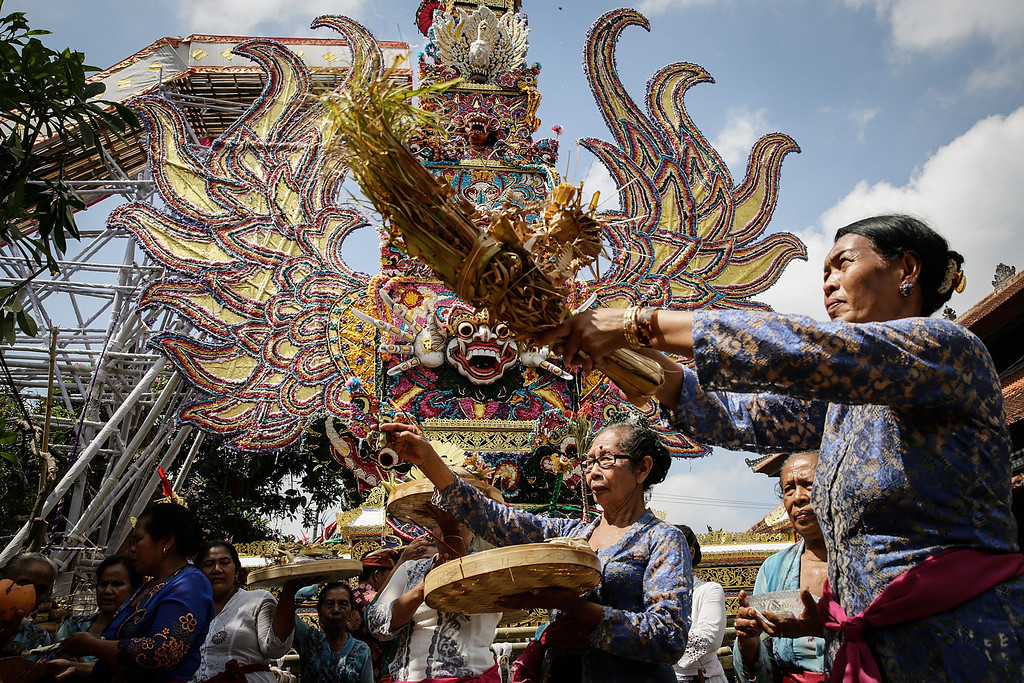 ". Balinese women give an offering and sprinkle holy water in front of the ""Bade\"" (body carrying tower) during the Royal cremation ceremony on November 1, 2013 in Ubud, Bali, Indonesia. (Photo by Agung Parameswara/Getty Images)"