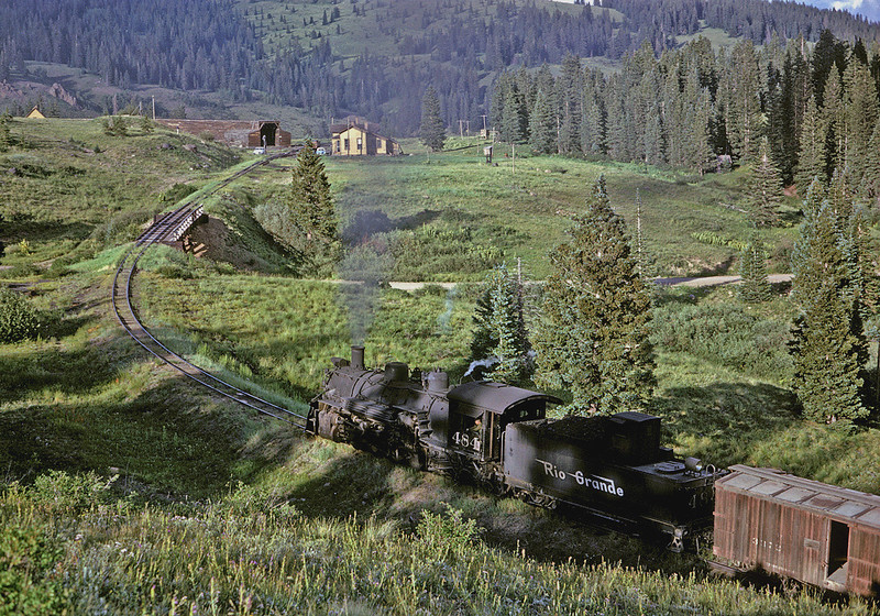 July 23,1963.It is late afternoon and the shadows are getting long as the 484 with its helper cut in ahead of the caboose pulls a Cumbres turn into the small yard at the top. This is a good overall view of Cumbes Pass as it used to be, as seen on the approach from Chama. In the distance the section house, snowshed over the wye, and water plug are visible. Near the left edge of the picture, peaking over the top of the low ridge, is the roof of the building that once was the home for a resident car inspector who inspected and repaired brakes prior to the decent down the 4 percent grade to Chama. In the the middle of the picture you can clearly see how the old road originally passed underneath the tracks west of the section house. Much remains the same today on the C&TS, but also much has changed. The road has been relocated and now crosses the railroad at grade on the other side of the section house, and the snowshed is gone.