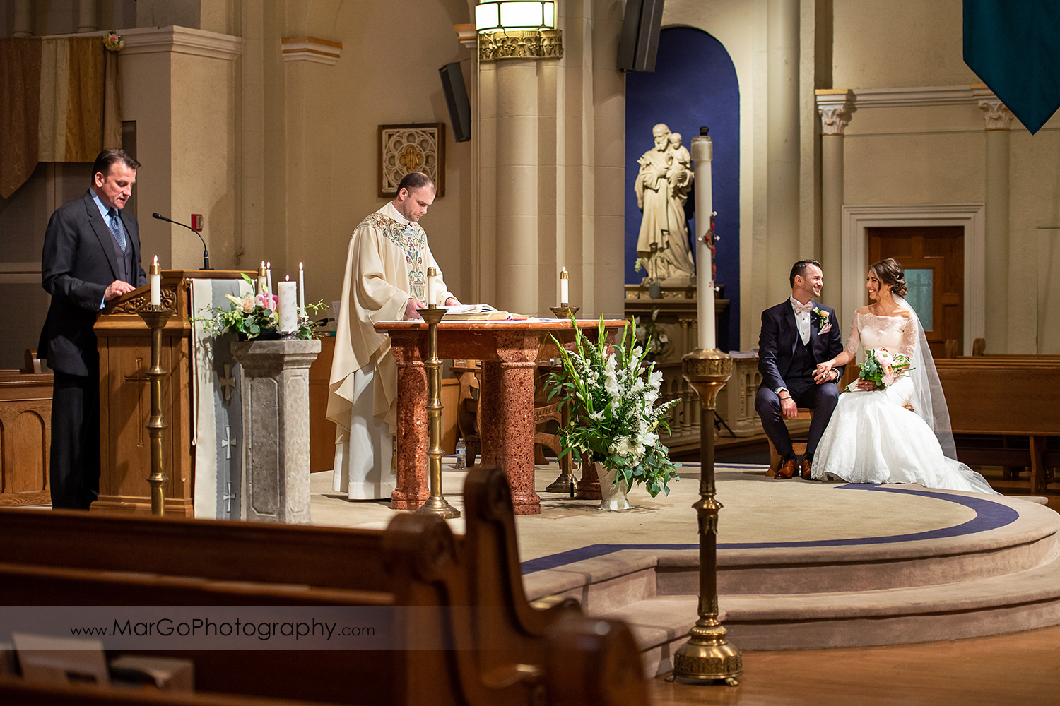 bride and groom sitting during wedding ceremony readings at Oakland Church of Saint Leo the Great