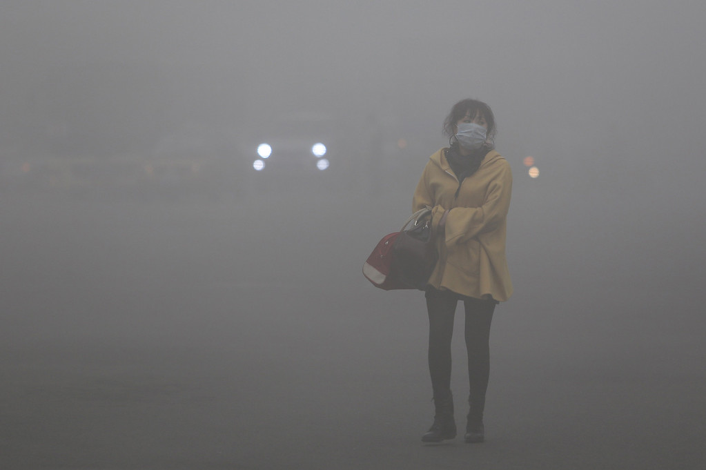 . A woman wearing a face mask walks in heavy smog in Haerbin, northeast China\'s Heilongjiang province, on October 21, 2013. Choking clouds of pollution blanketed Haerbin, a Chinese city famed for its annual ice festival on October 21, reports said, cutting visibility to 10 metres (33 feet) and underscoring the nation\'s environmental challenges.  AFP PHOTOSTR/AFP/Getty Images