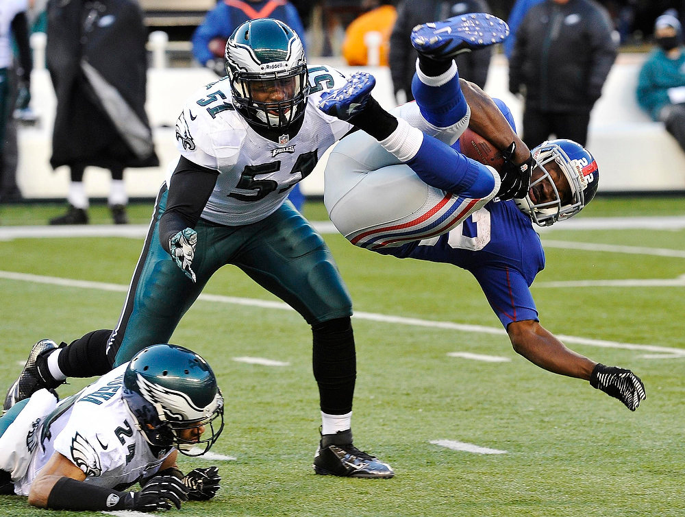 Description of . New York Giants David Wilson (R) is tackled by Philadelphia Eagles Nnamdi Asomugha (L) and Jamar Chaney (C) in the third quarter of their NFL football game in East Rutherford, New Jersey, December 30, 2012. REUTERS/Ray Stubblebine