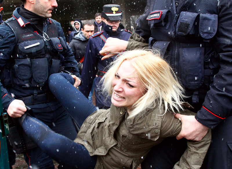 ". Police take away a woman protesting where former Italian Premier Silvio Berlusconi was voting, in Milan, Italy, Sunday, Feb. 24, 2013.  When Berlusconi showed up at a Milan polling place to cast his ballot, three women pulled off their sweaters to bare their breasts and display the slogan ""Basta Silvio!\"" (Enough of Silvio) scrawled on their flesh. A cordon of police, already in place for security before the former premier\'s arrival, blocked Berlusconi\'s direct view of the women. Police detained the women for questioning. Italian news reports said the three were members of the Femen protest group. Italy votes in a watershed parliamentary election Sunday and Monday that could shape the future of one of Europe\'s biggest economies. (AP Photo/Spada, Lapresse)"