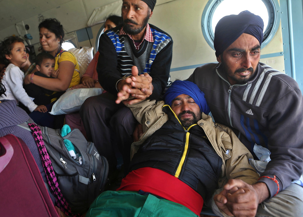 . Tears roll down the cheeks of a relative of a seriously ill tourist as they hold him inside an Indian air force helicopter after being rescued from a flooded neighborhood in Srinagar, Indian-controlled Kashmir, Wednesday, Sept.10, 2014. (AP Photo/Dar Yasin)