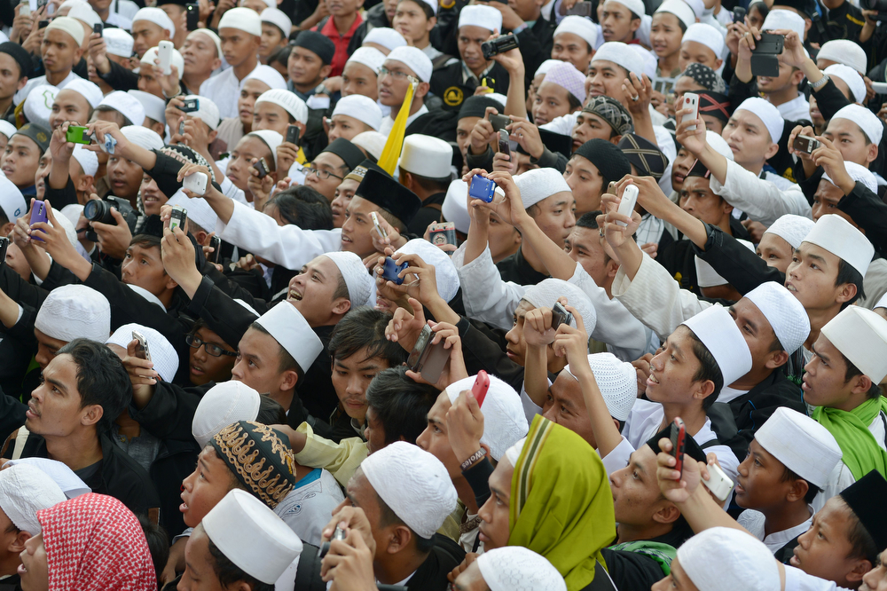 . Indonesian Muslim youths take pictures of a cleric during a mass prayer to celebrate Muhammad\'s birthday in Jakarta on January 14, 2014. Thousands of Muslims in Indonesia celebrated the birthday of prophet Muhammad called Mawlid or locally maulud, which occurs in the third month in the Islamic calendar. (ADEK BERRY/AFP/Getty Images)
