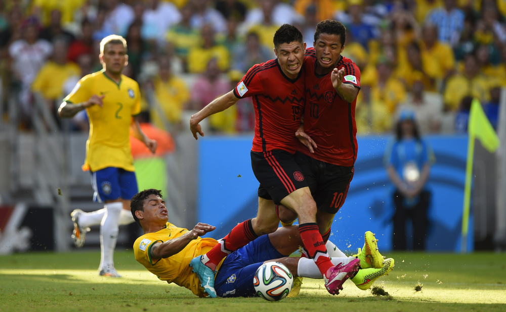 . Brazil\'s defender Thiago Silva (down) vies with Mexico\'s forward Giovani Dos Santos (R) and Mexico\'s forward Oribe Peralta (C) during a Group A football match between Brazil and Mexico in the Castelao Stadium in Fortaleza during the 2014 FIFA World Cup on June 17, 2014. (ODD ANDERSEN/AFP/Getty Images)