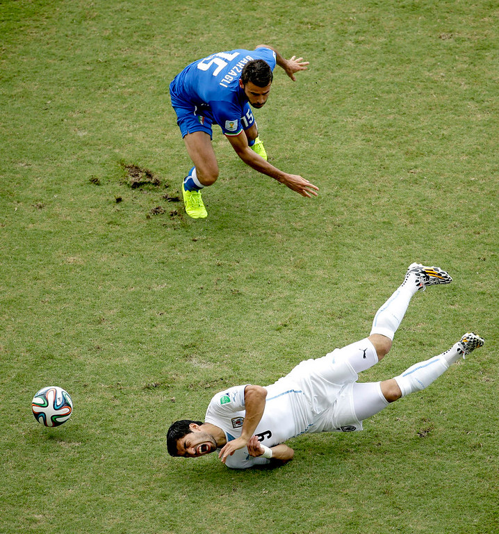 . Uruguay\'s Luis Suarez (9) falls to the pitch as Italy\'s Andrea Barzagli (15) watches during the group D World Cup soccer match between Italy and Uruguay at the Arena das Dunas in Natal, Brazil, Tuesday, June 24, 2014. (AP Photo/Hassan Ammar)