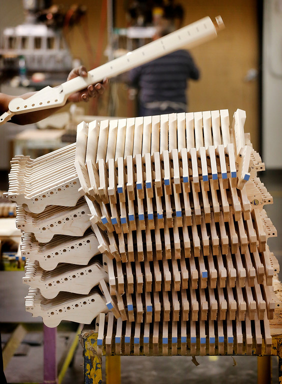 . Fender Stratocaster electric guitar necks are prepared for assembly at the Fender factory in Corona, Calif. Leo Fender developed the instrument in a small workshop in Fullerton, Calif. six decades ago. (AP Photo/Matt York)