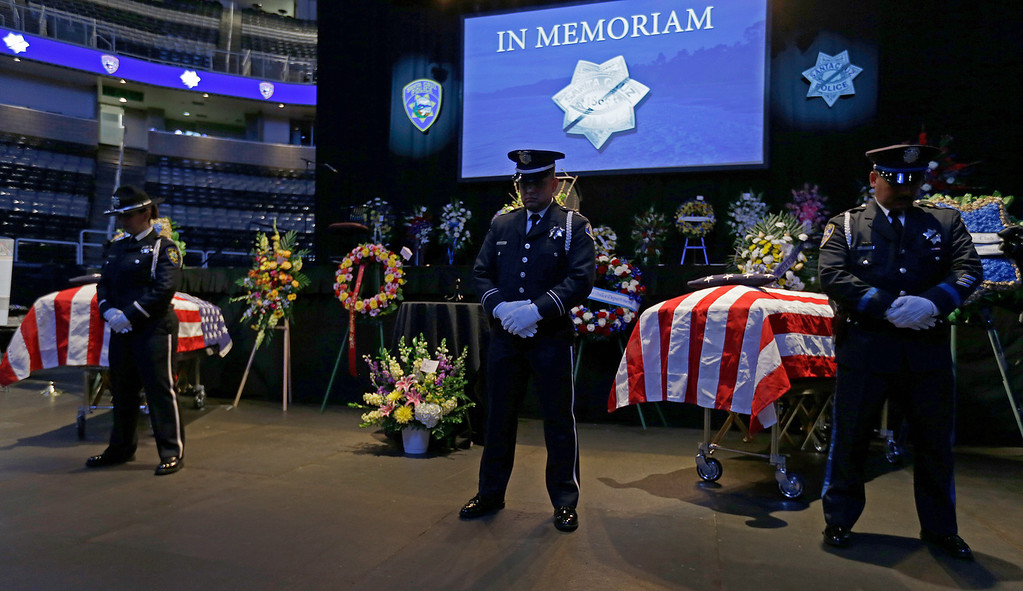 . Police stand guard over the caskets of slain Santa Cruz police Sgt. Loran Baker and Detective Elizabeth Butler at a memorial service Thursday, March 7, 2013, at HP Pavilion  in San Jose, Calif. Baker and Butler were shot to death on Feb. 26, after arriving at the home of Jeremy Peter Goulet to question him about a misdemeanor sexual assault. (AP Photo/Ben Margot)