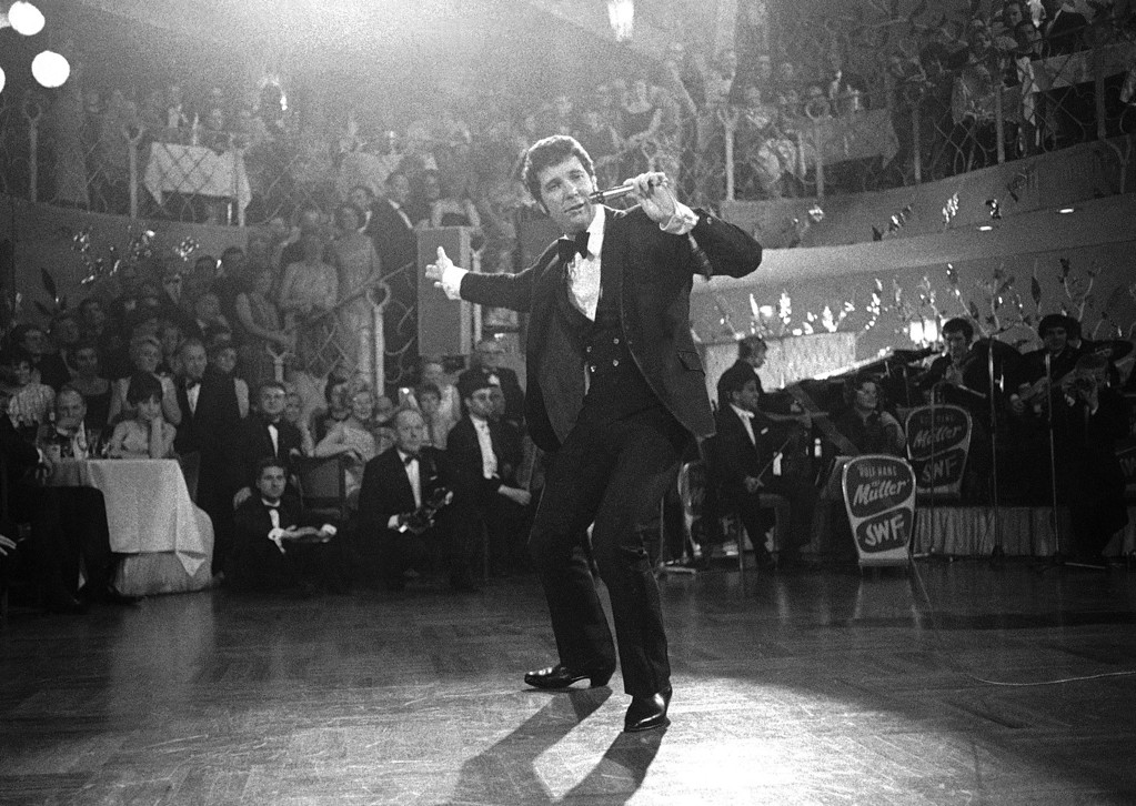 """. British pop singer Tom Jones during his performance at the \""""Bal Pare\"""", in Munich, Germany, on Jan. 21, 1968. Jones was showered with flowers during his performance. This festival is one of the most famous carnival-balls of Germany. (AP Photo)"""