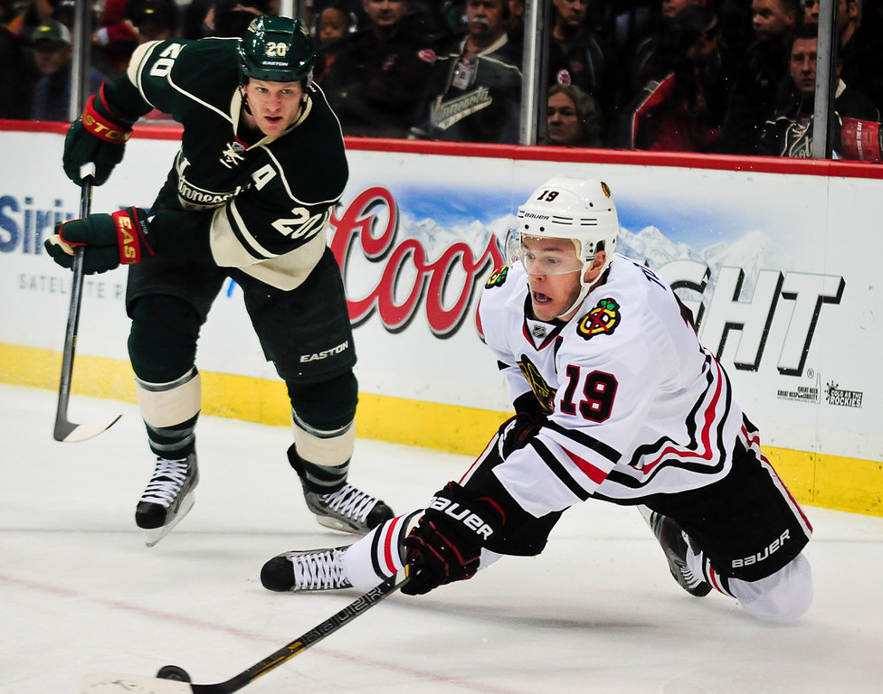 . Chicago center Jonathan Toews, right, takes a diving shot on goal as he\'s covered by Minnesota defenseman Ryan Suter in the first period. (Pioneer Press: Ben Garvin)