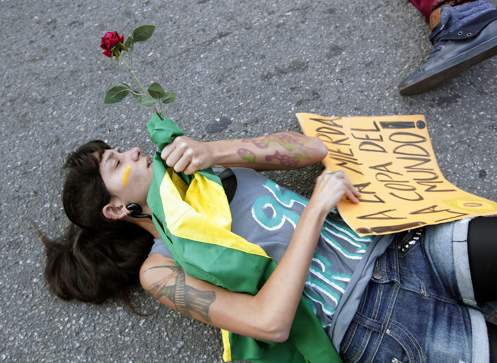 . A protester lies on the ground in front of a police line in Rio de Janeiro, Brazil, Sunday, June 16, 2013. Brazilian police dispersed a small protest against a public transport fare hike that broke out in front of Rio de Janeiro\'s Maracana stadium ahead of the Mexico-Italy soccer match during the Confederations Cup. (AP Photo/Bruno Magalhaes)