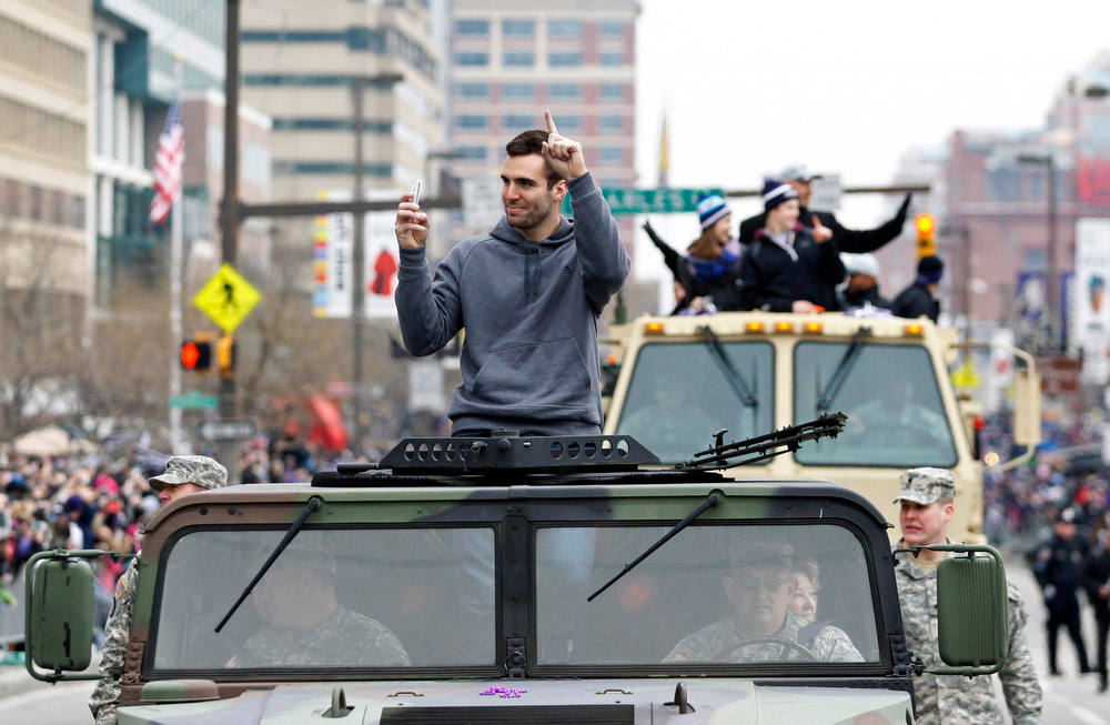 Description of . Baltimore Ravens quarterback and Super Bowl MVP Joe Flacco waves to the crowd gathered on the team\'s parade route in Baltimore, Maryland February 5, 2013. The Ravens defeated the San Francisco 49ers to win the NFL championship.  REUTERS/Richard Clement
